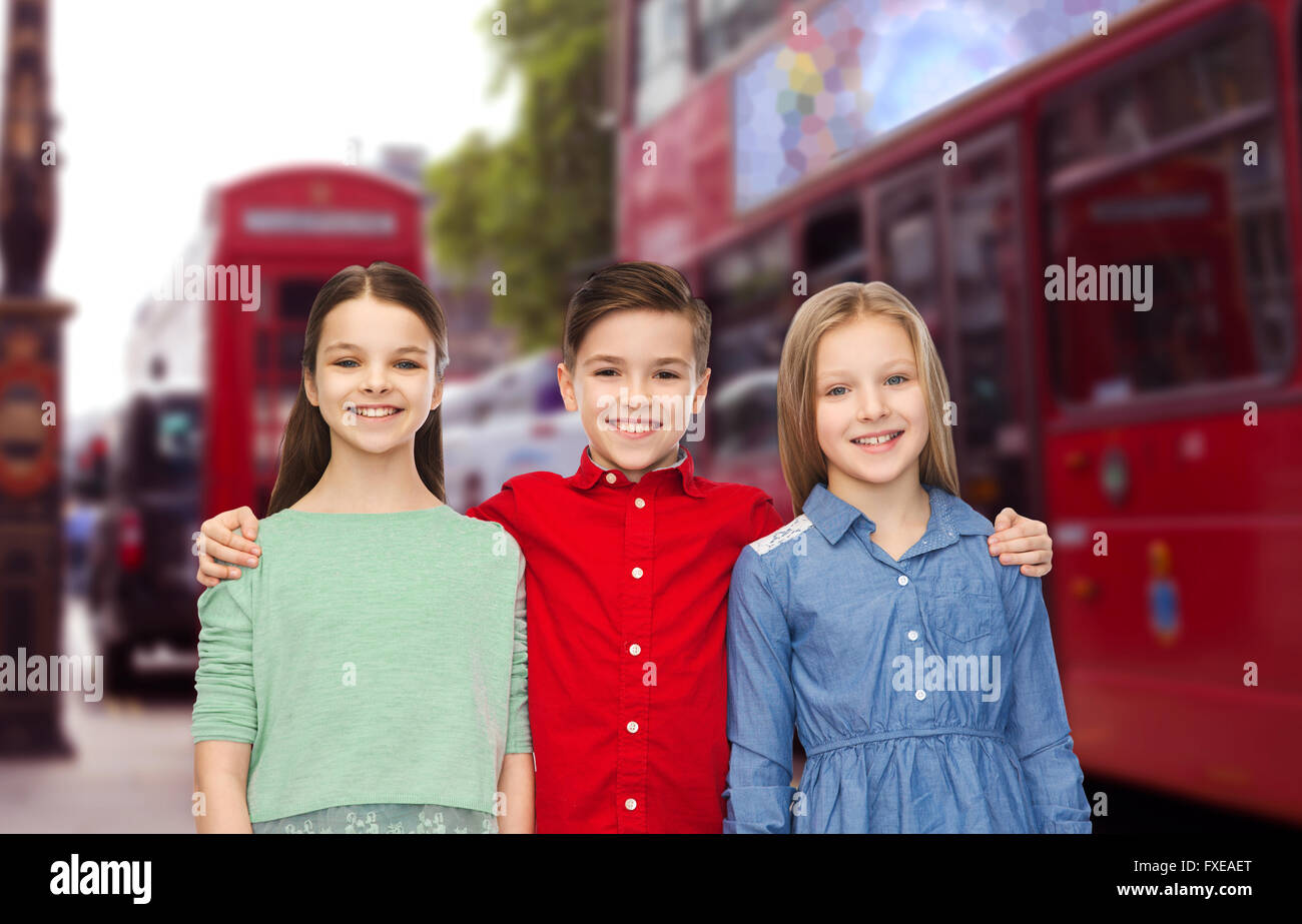 happy boy and girls hugging over london city - Stock Image