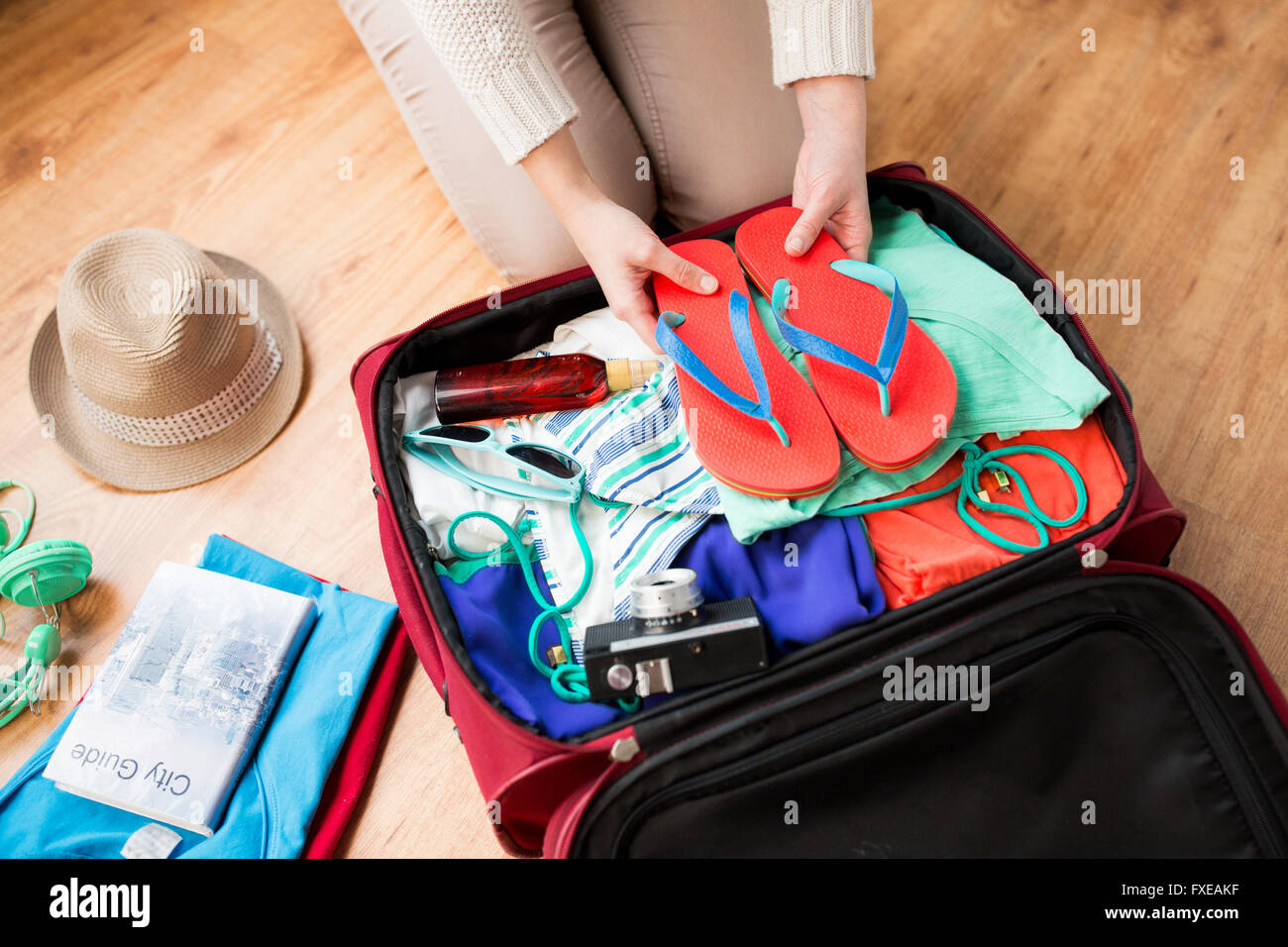 close up of woman packing travel bag for vacation stock photo