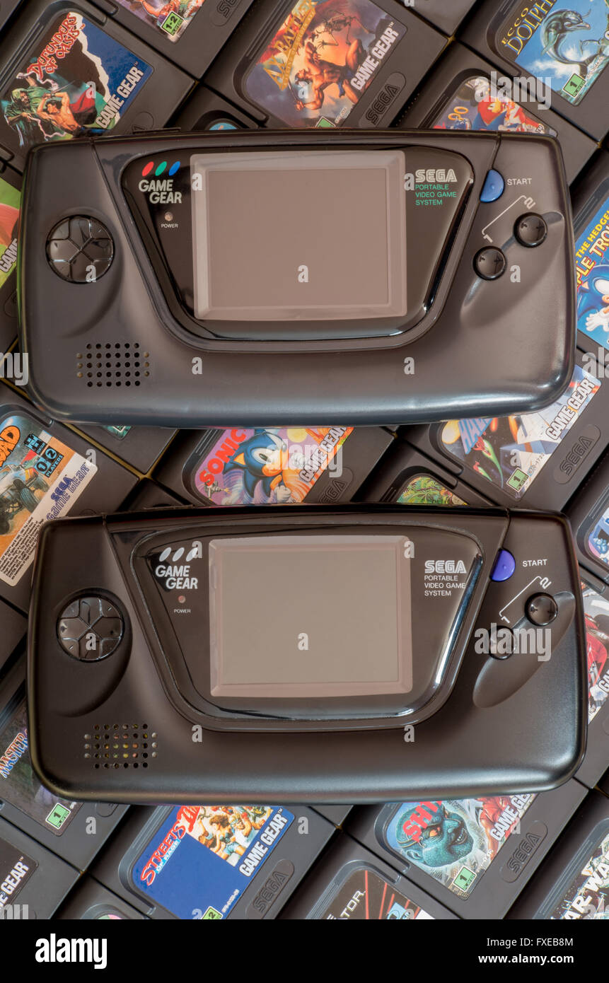 Two Sega Game Gear video game units - the original 1990 release and the Majesco version from 2001 - on a bed of Stock Photo