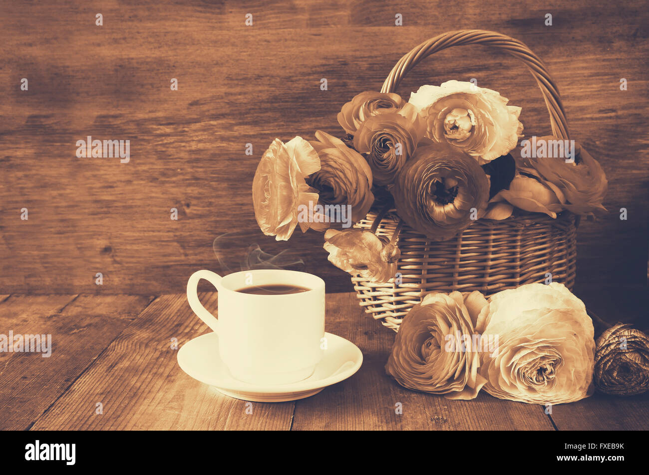 image of beautiful flowers next to cup of coffee. sepia style vintage filtered. - Stock Image