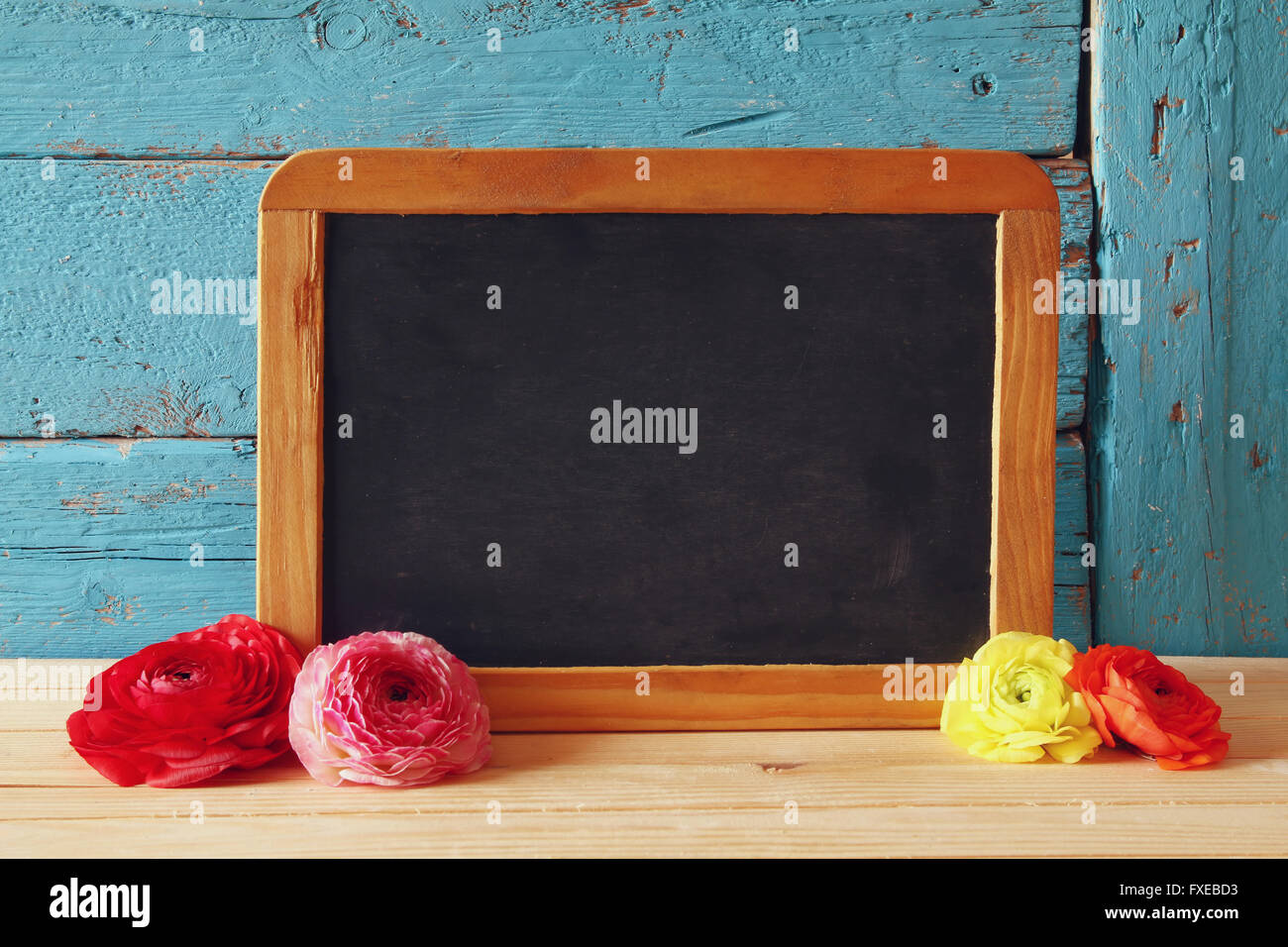 flowers next to empty blackboard, on wooden table. copy space. - Stock Image