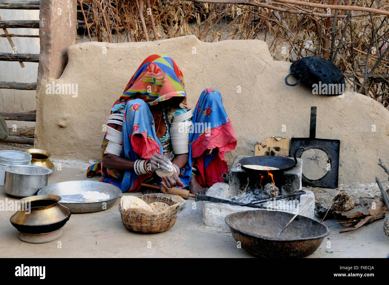 A woman sits making her early morning breakfast chapatis in a village near the northern Indian town of Jojawar. - Stock Image