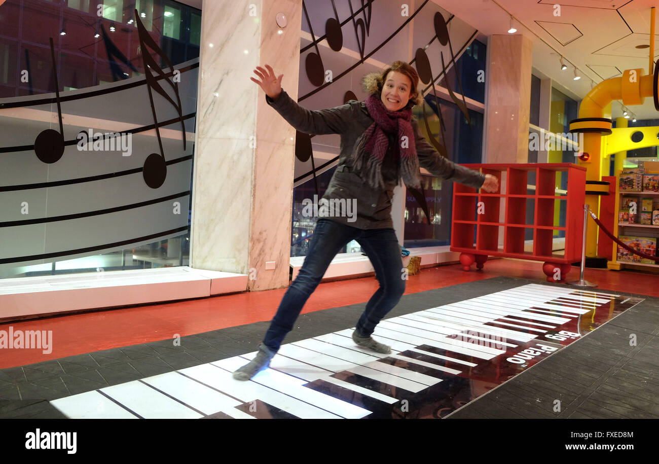 A tourist on the Big Piano made famous in the movie Big in F.A.O. Schwarz toy store New York City, USA. - Stock Image