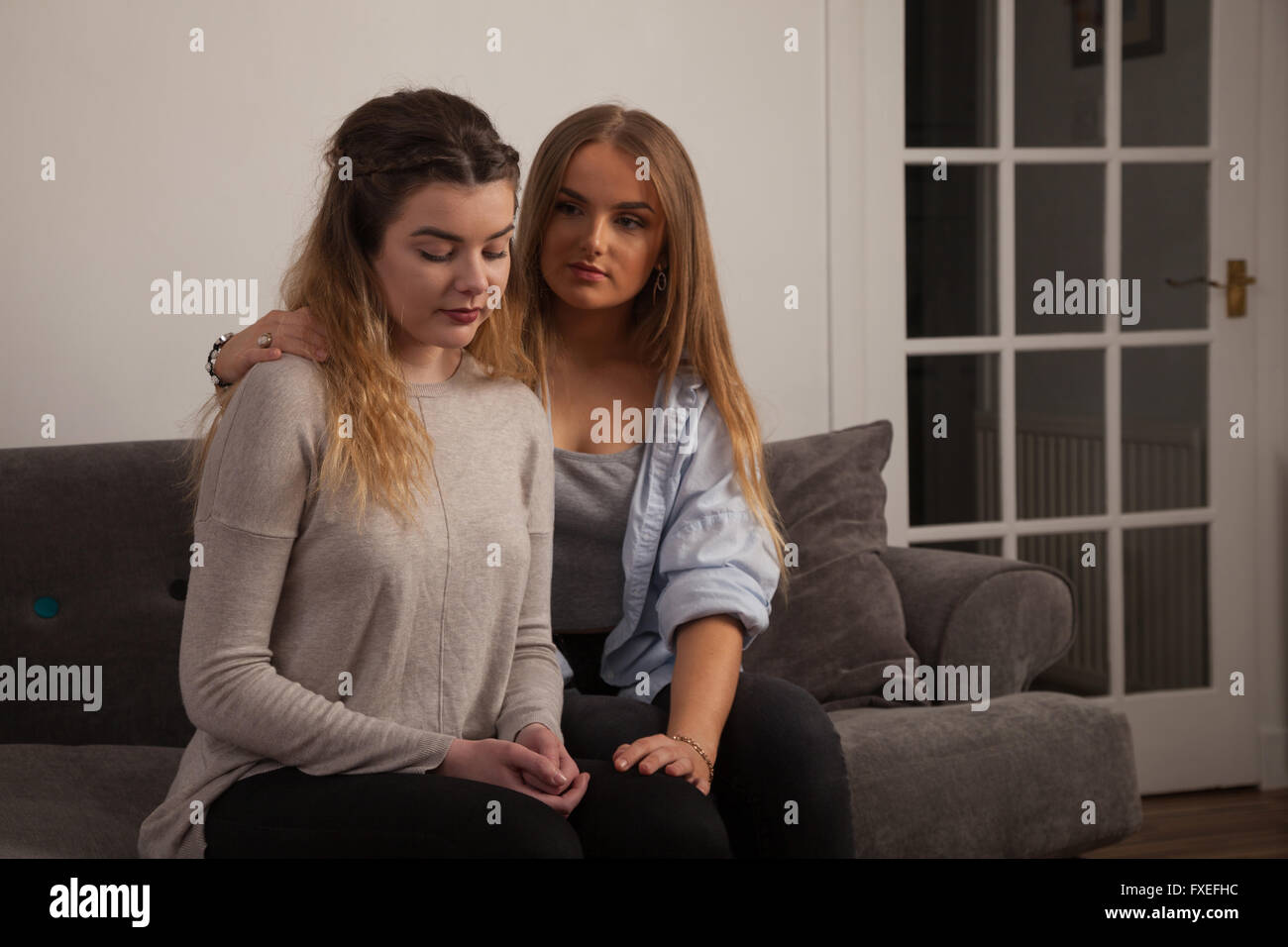 Two young women comforting each other at home on a sofa. Stock Photo