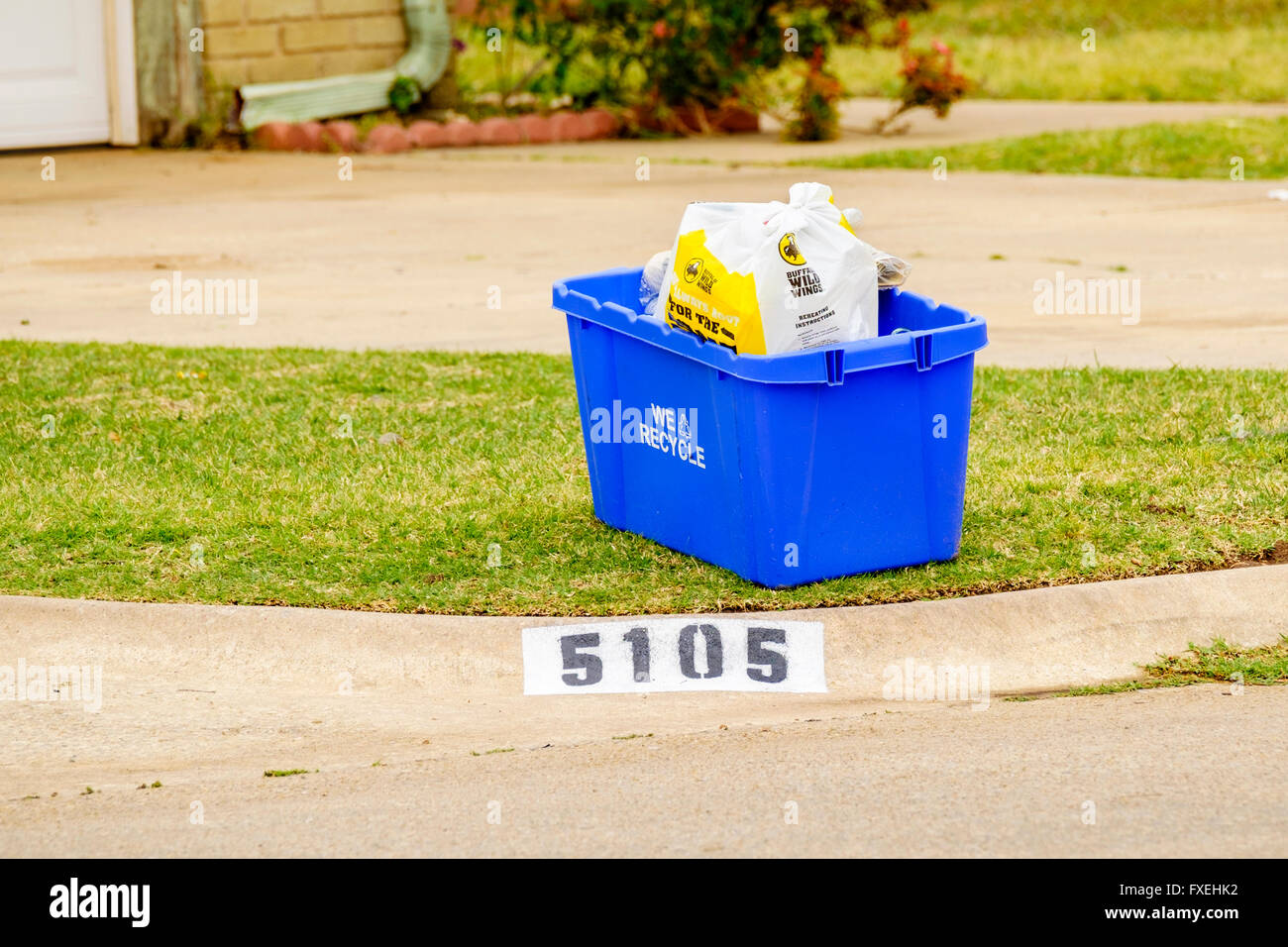 A blue plastic bin with recyclables waiting for pick up in Oklahoma City, Oklahoma, USA. - Stock Image