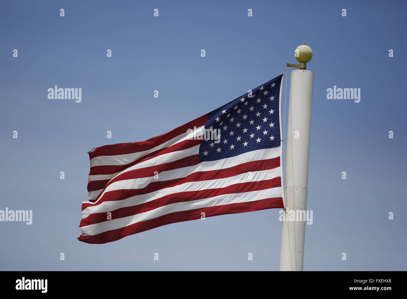 Unites States flag flying on cell phone tower. - Stock Image