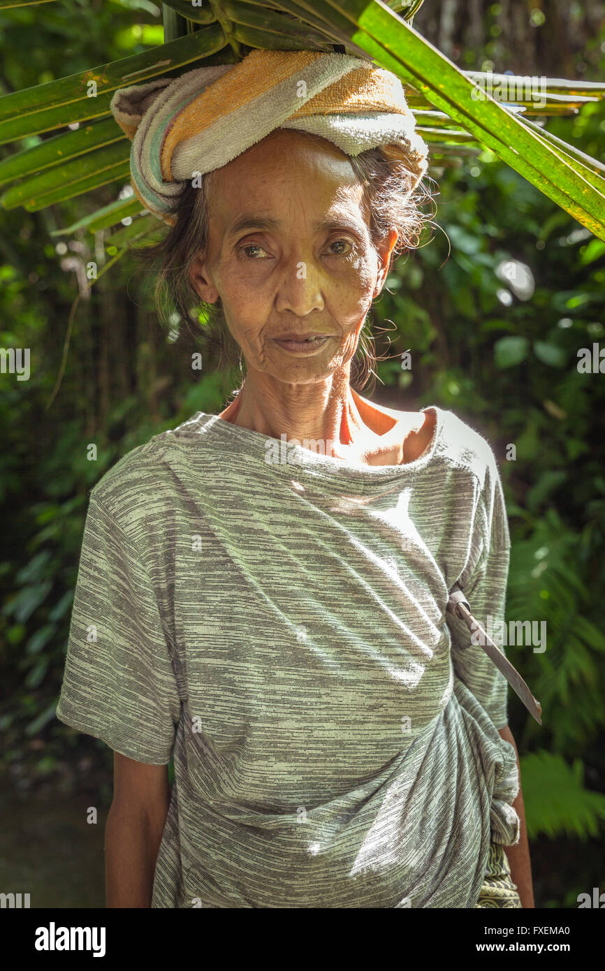 Ubud, Indonesia - February 28, 2016: Portrait of senior Balinese woman carrying leafs on the head, Ubud, Bali, Indonesia. Stock Photo