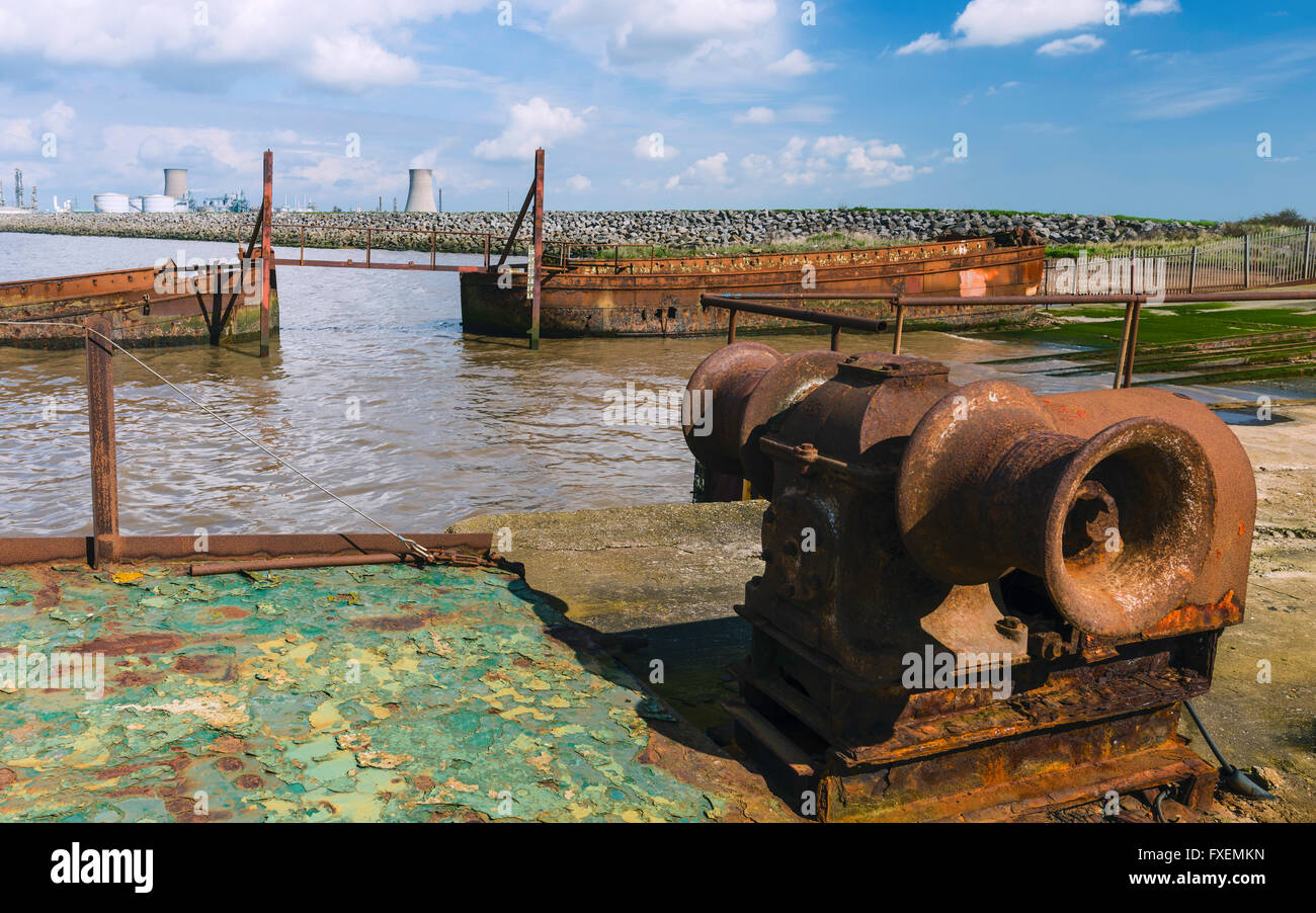Rusting machinery, and obsolete, abandoned river boats beached on the mud banks of the Humber estuary at high tide. - Stock Image