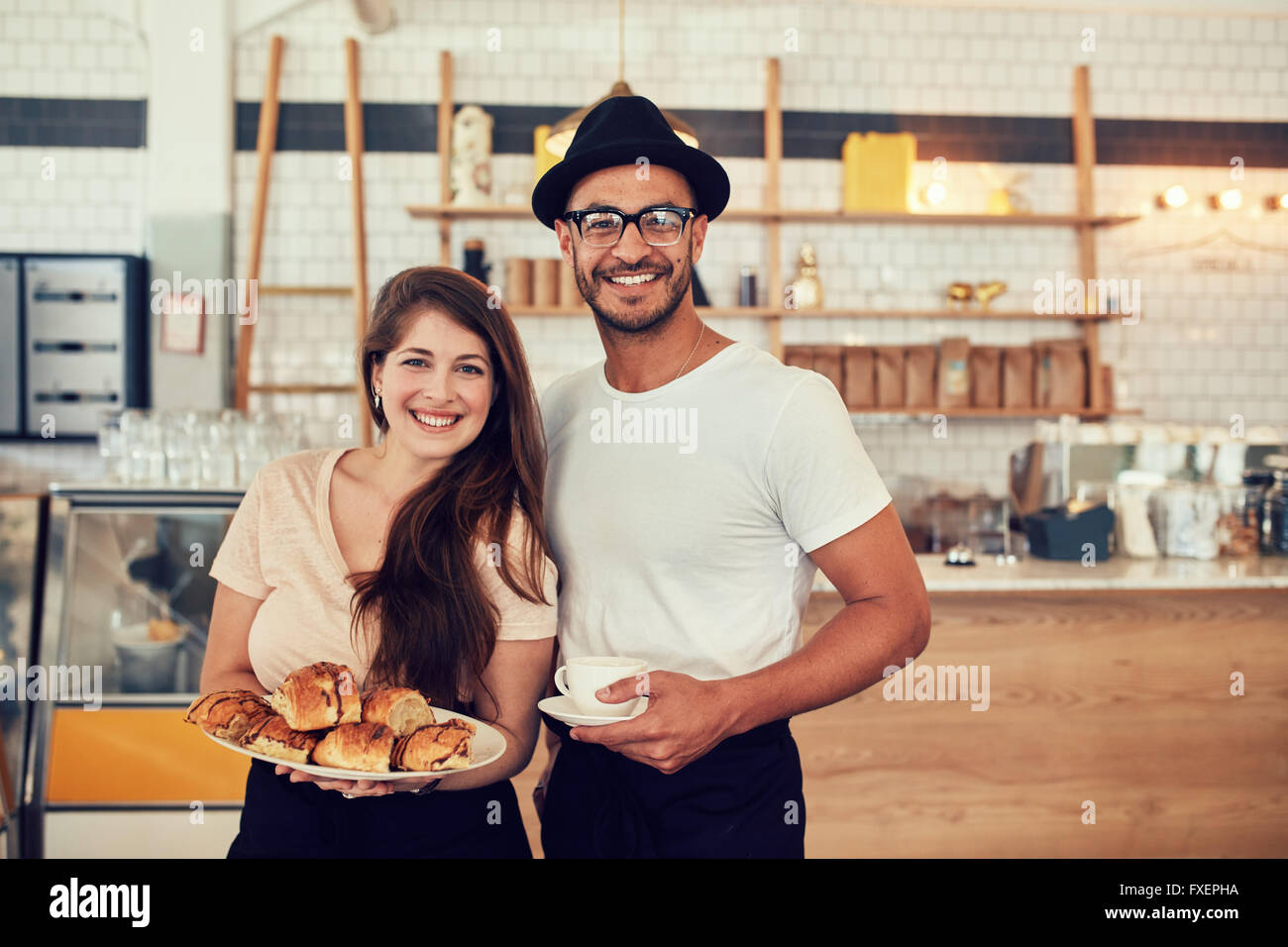Portrait of happy young man and woman with food and cafe at coffee shop. Couple having food in a restaurant. - Stock Image