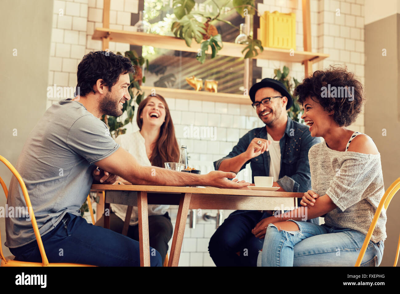 Young friends having a great time in restaurant. Group of young people sitting in a coffee shop and smiling. - Stock Image