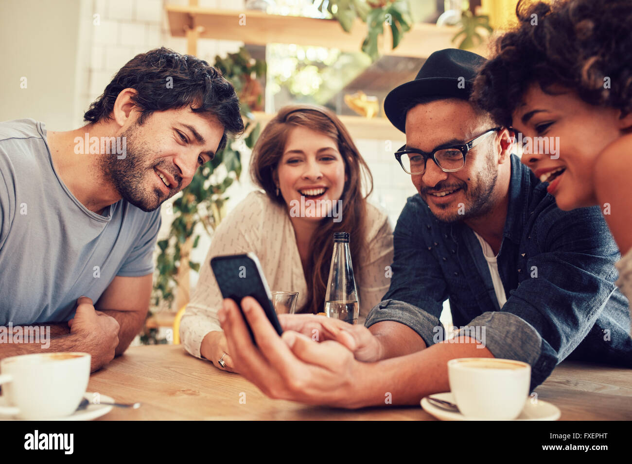 Group of young people sitting in a cafe and looking at the photos on smart phone. Young men and women meeting at - Stock Image