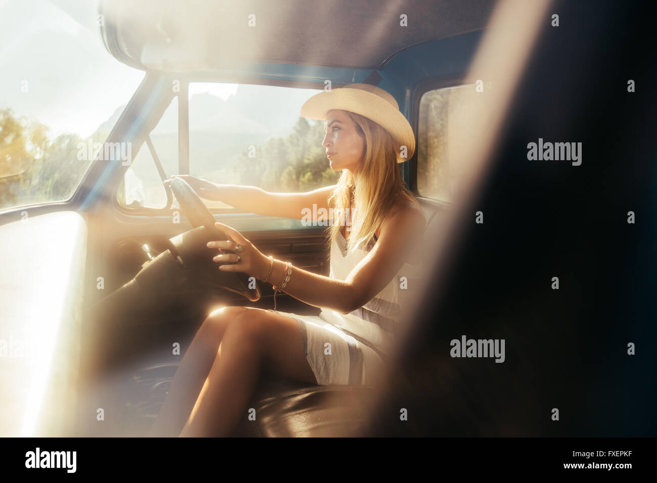 Portrait of beautiful young woman wearing a hat driving a car on sunny day. Young girl on a road trip. Stock Photo