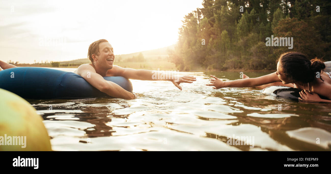 Loving young couple about to hold hands while floating on inner tubes in lake. Young man and woman on an inflatable - Stock Image