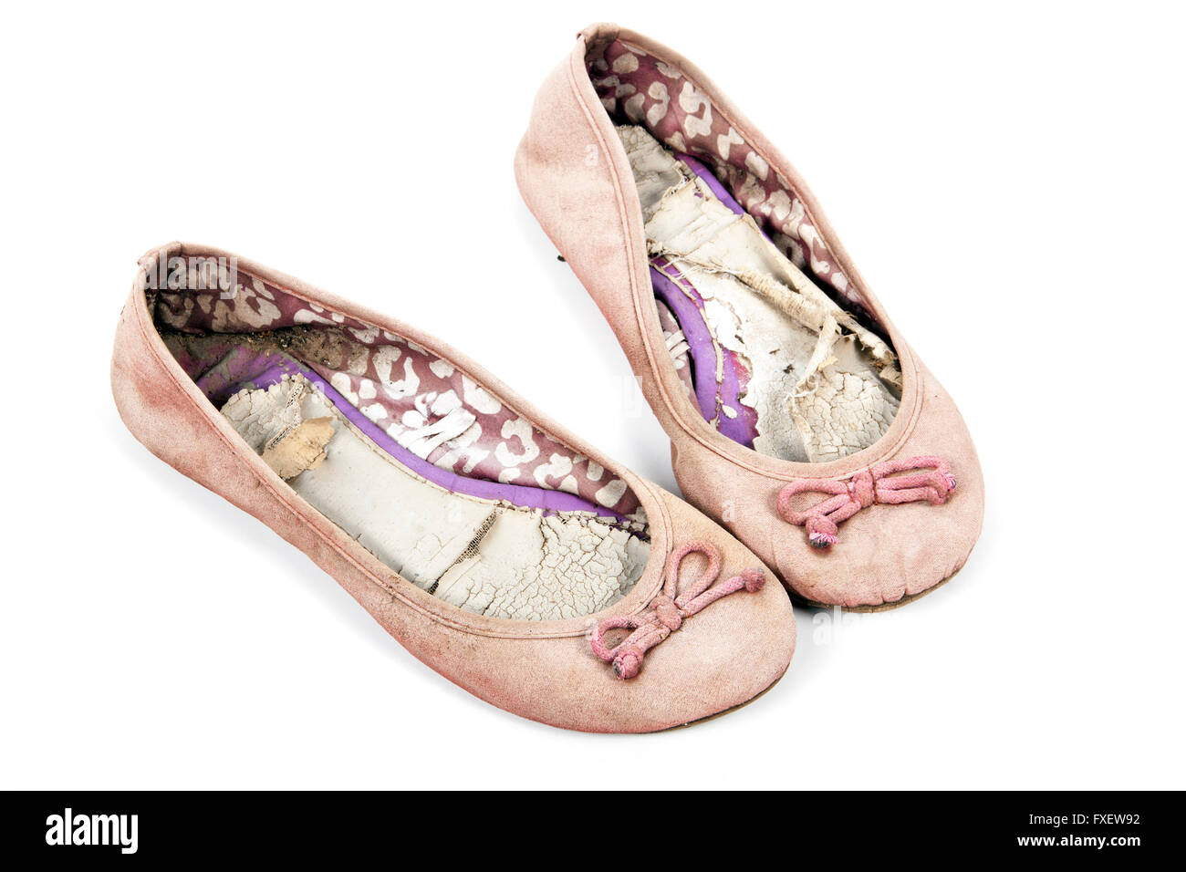 Pair of old well used  pink tattered female worn-out shoes on white - Stock Image
