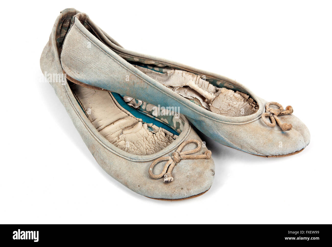 Pair of old well used blue tattered female worn-out shoes on white - Stock Image