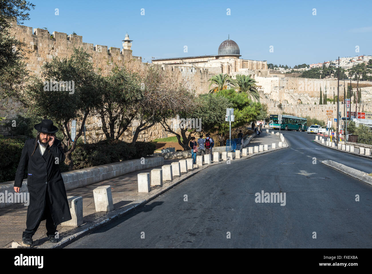 Orthodox Jew on Ma'ale HaShalom street called Pope's Road in Jerusalem, Israel. Al-Aqsa Mosque on background - Stock Image