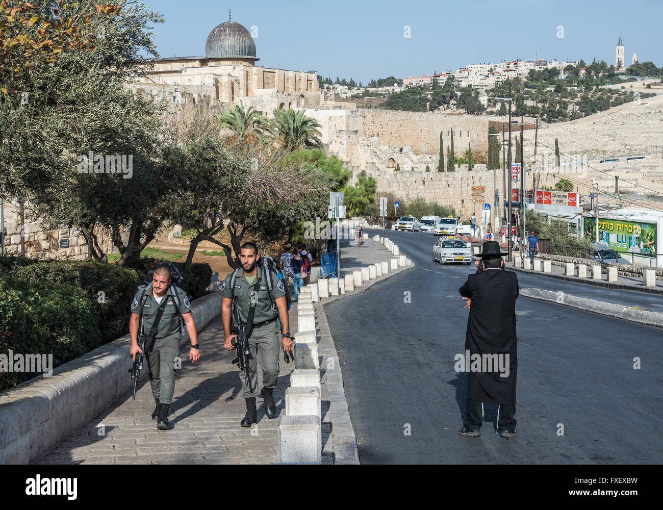 Orthodox Jew and Israeli Border Police patrol on Ma'ale HaShalom street in Jerusalem, Israel. Al-Aqsa Mosque - Stock Image