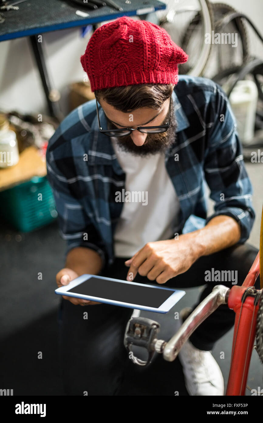 Bike mechanic looking at tablet computer - Stock Image