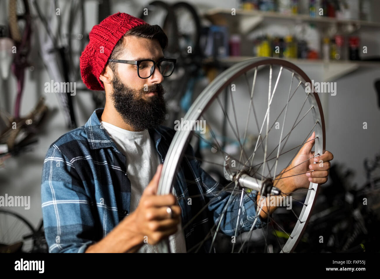 Bike mechanic checking at wheel - Stock Image