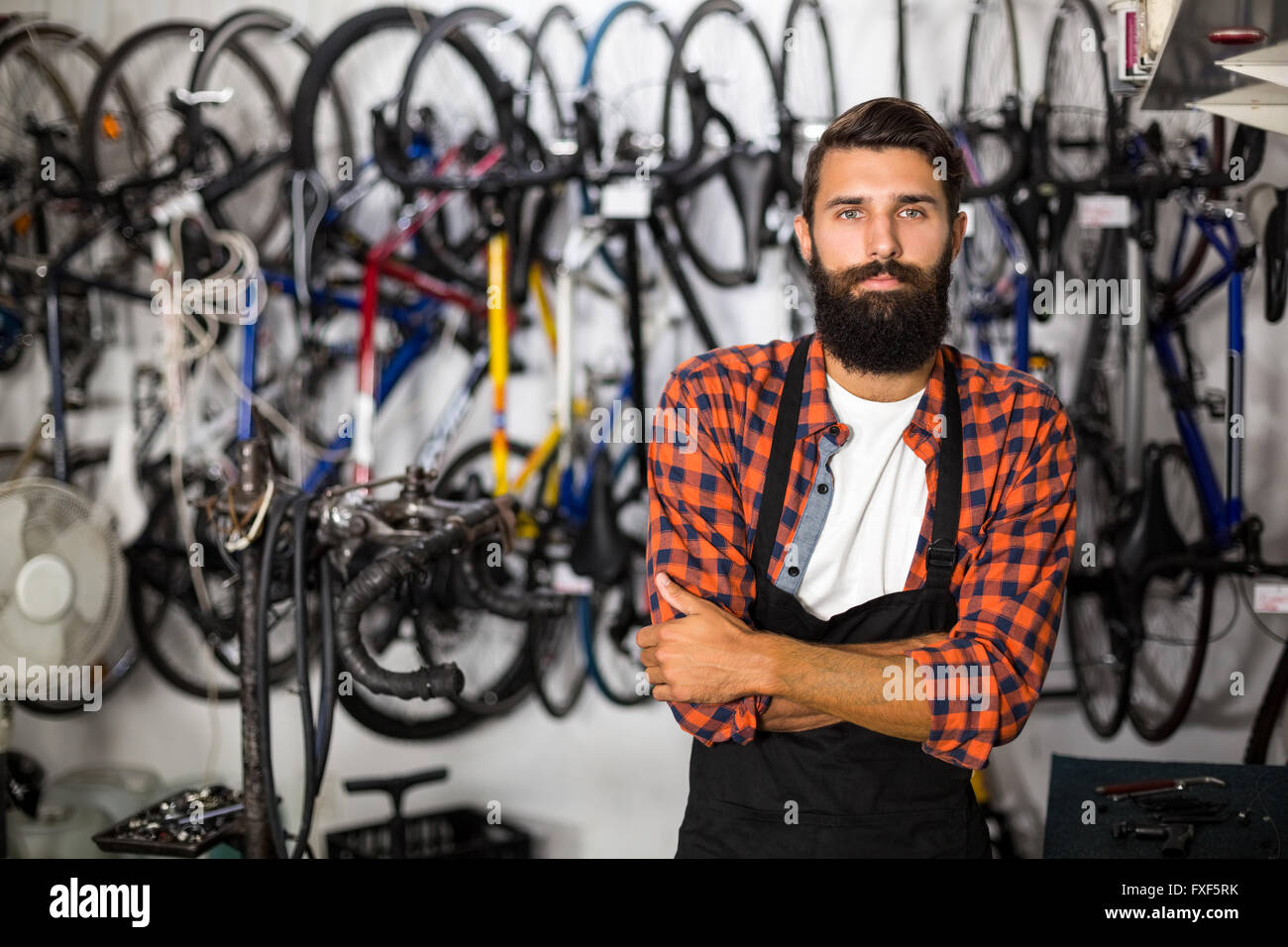 Bike mechanic standing with arms crossed - Stock Image