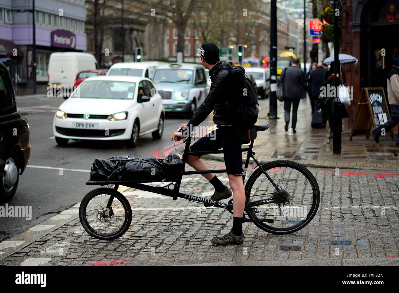 Cycle courier amongst traffic in wet weather in London Stock