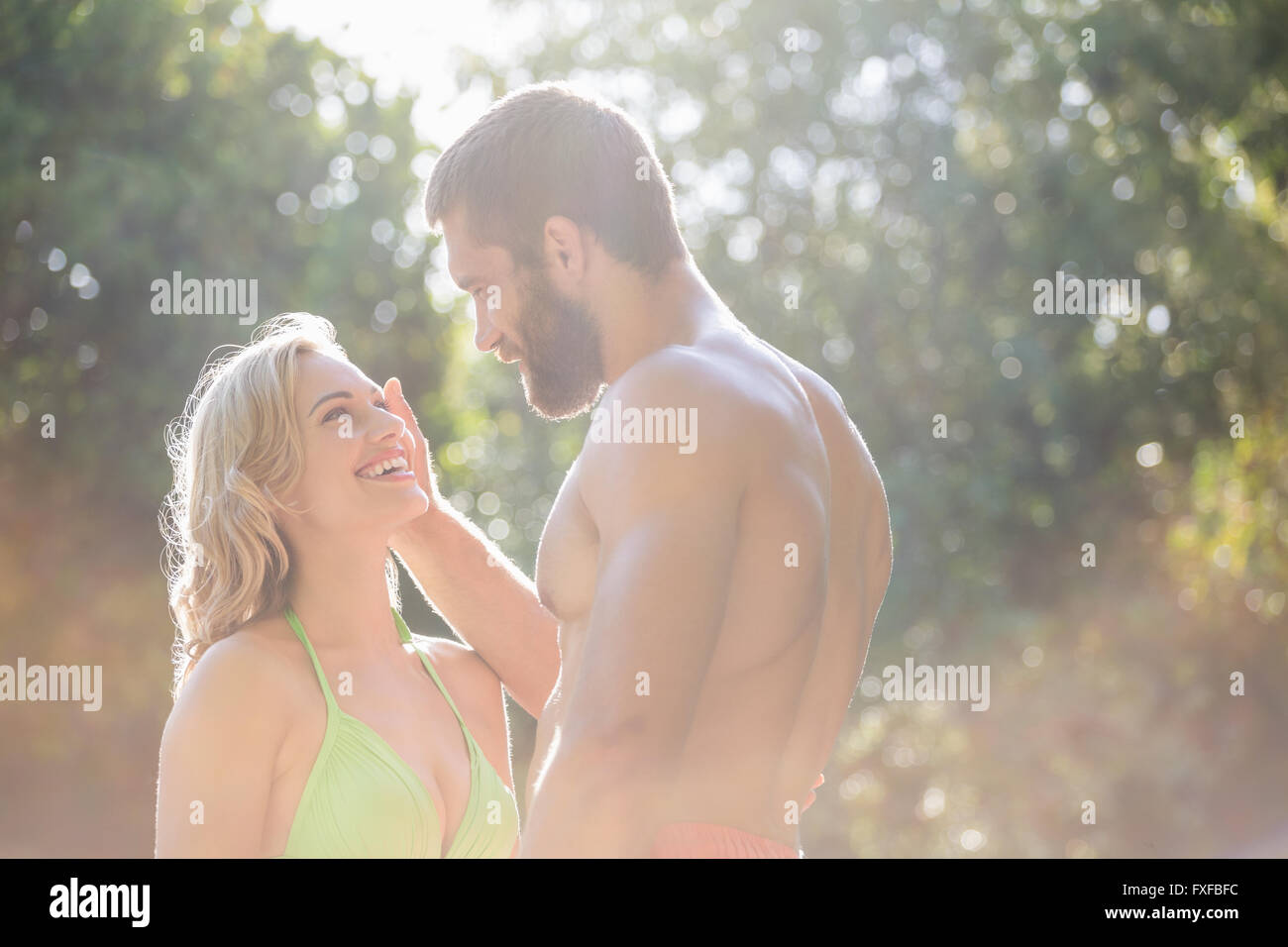 Happy couple in swimwear looking face to face - Stock Image