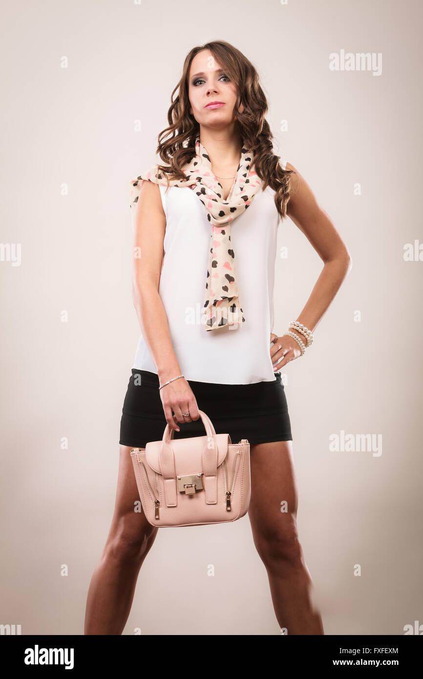 046d9dbc8add Elegant outfit. Female fashion. Girl in fashionable clothes holding bag  handbag studio shot on gray background