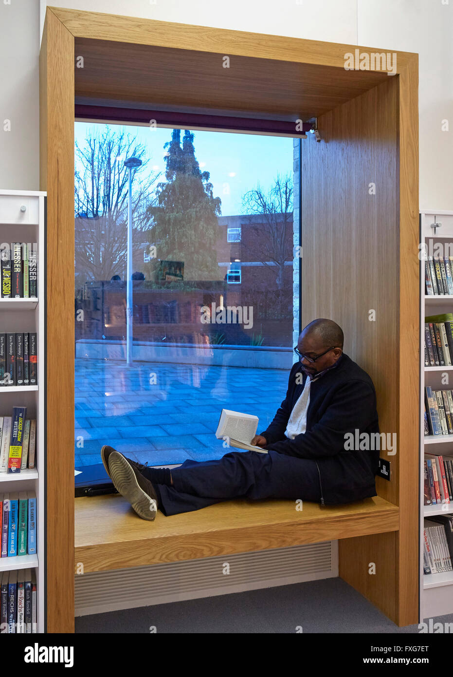 Interior view showing recessed window seat with man reading. Camberwell Library, London, United Kingdom. Architect: - Stock Image