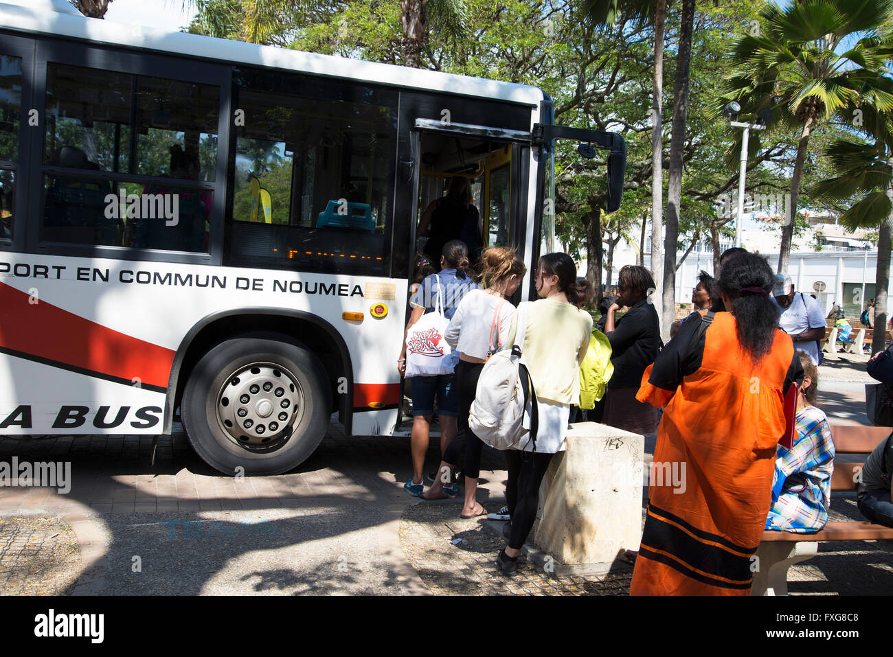 passengers queue to get on single decker bus in Noumea central square - Stock Image