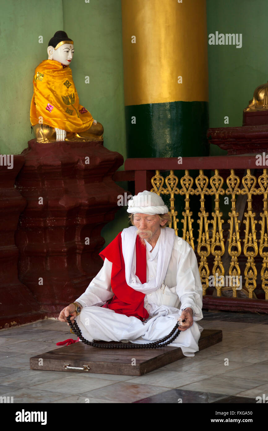 A cross-legged worshipper praying in an annex of the Paya Shwedagon, in Yangon (Myanmar) Croyant priant dans le - Stock Image