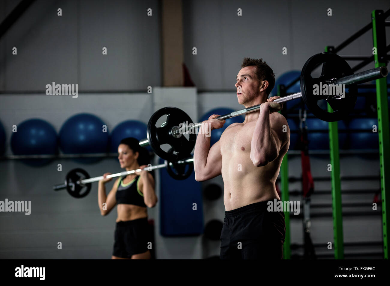 Man and woman lifting barbell - Stock Image