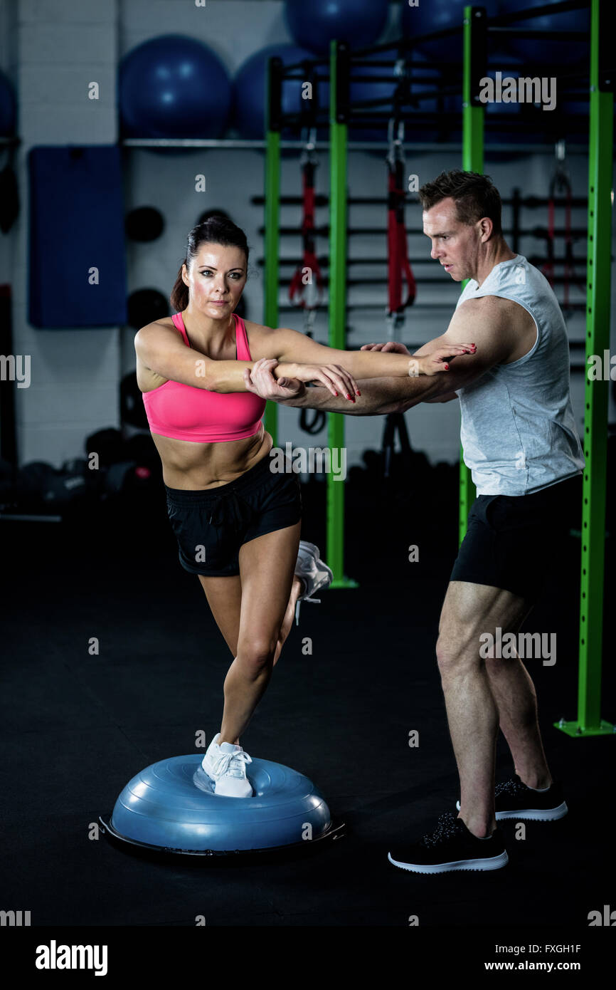 Trainer assisting a woman standing on a bosu ball - Stock Image