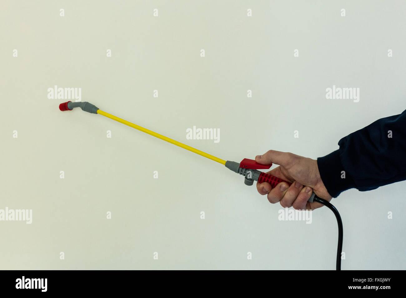 Mans hand spraying pesticide - Stock Image