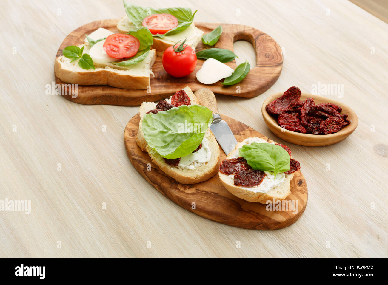 Open-faced sandwiches made of ciabatta, sun dried tomatoes, creamy cheese and lettuce leaf basil. Antipasti - Stock Image