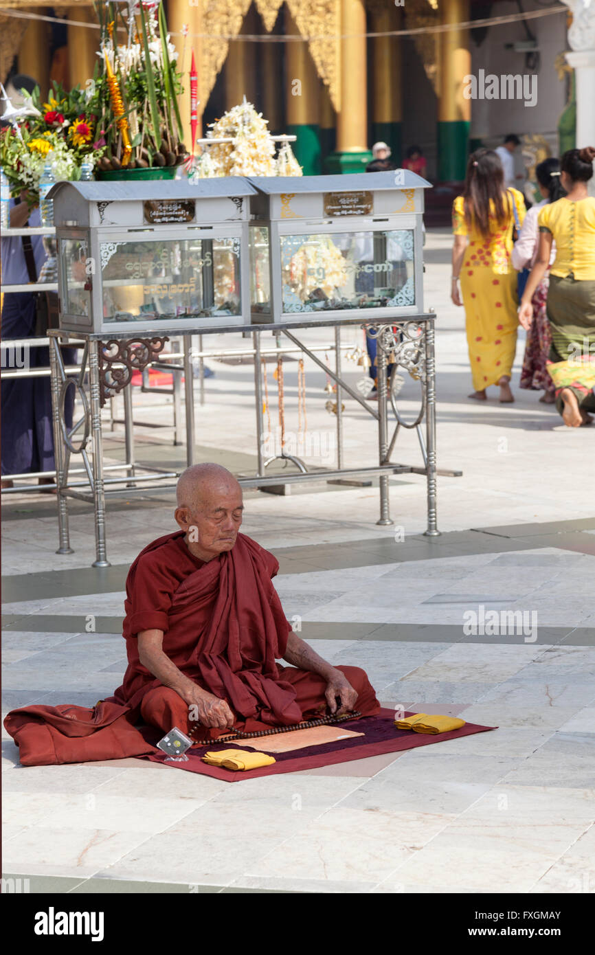 A cross-legged monk praying in front of an annex of the Paya Shwedagon, in Yangon (Myanmar). Moine assis en tailleur - Stock Image