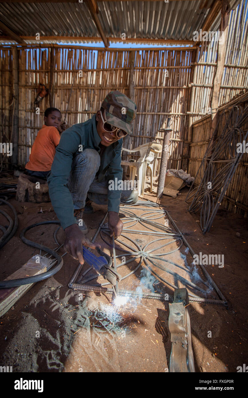 mozambique, a man and a child welding in a locksmith bodyshop - Stock Image