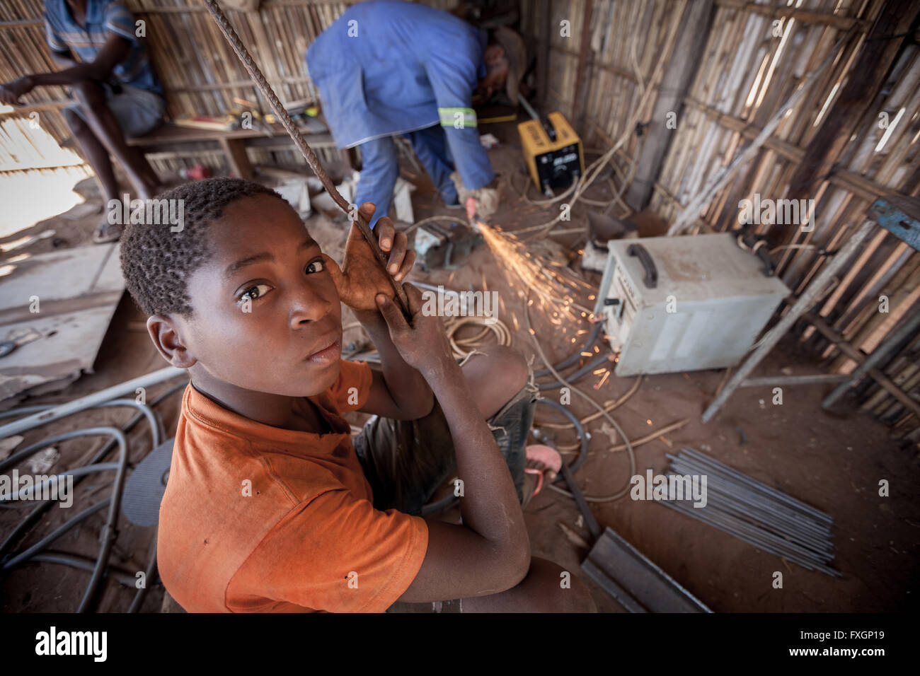 mozambique, a child works in a locksmith bodyshop - Stock Image