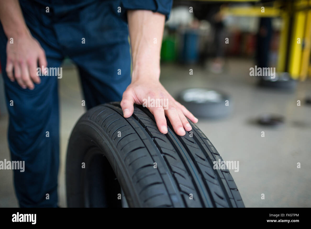 Mechanic pushing a tyre - Stock Image