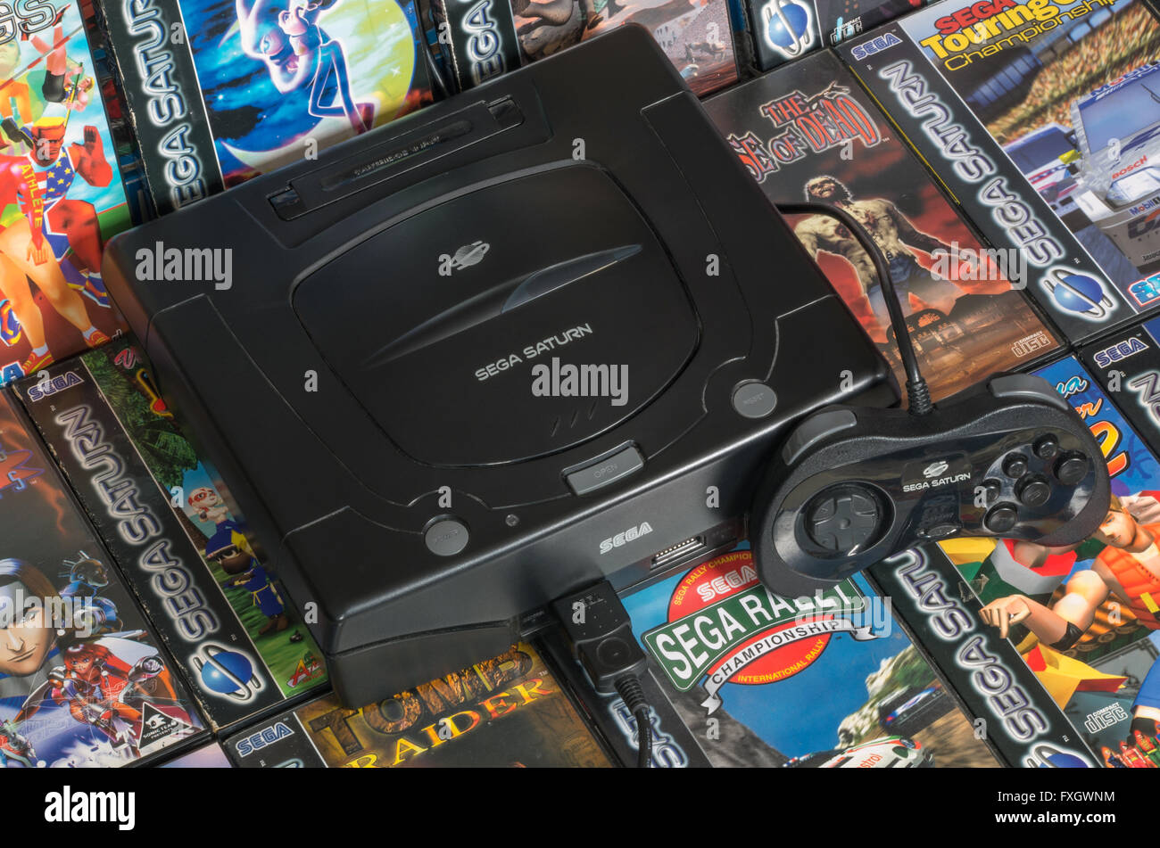 A PAL Sega Saturn console with a standard controller on a bed of its best games. - Stock Image