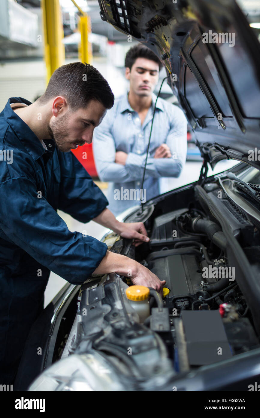Mechanic examining car engine while customer standing and looking - Stock Image