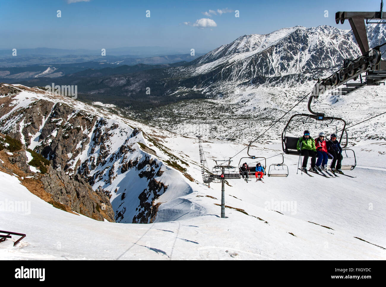 End of skiing season on Kasprowy Wierch. Ski slopes and skiers on the chairlift at Hala Gasienicowa in Tatra mountains - Stock Image