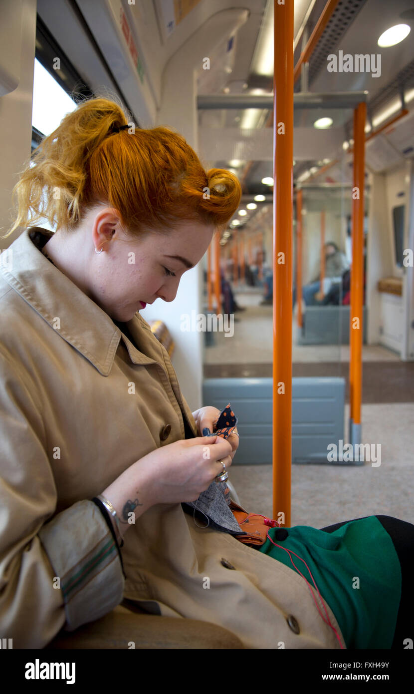A redhead embroidering on the 'ginger' line, (The London Overground) North London. - Stock Image