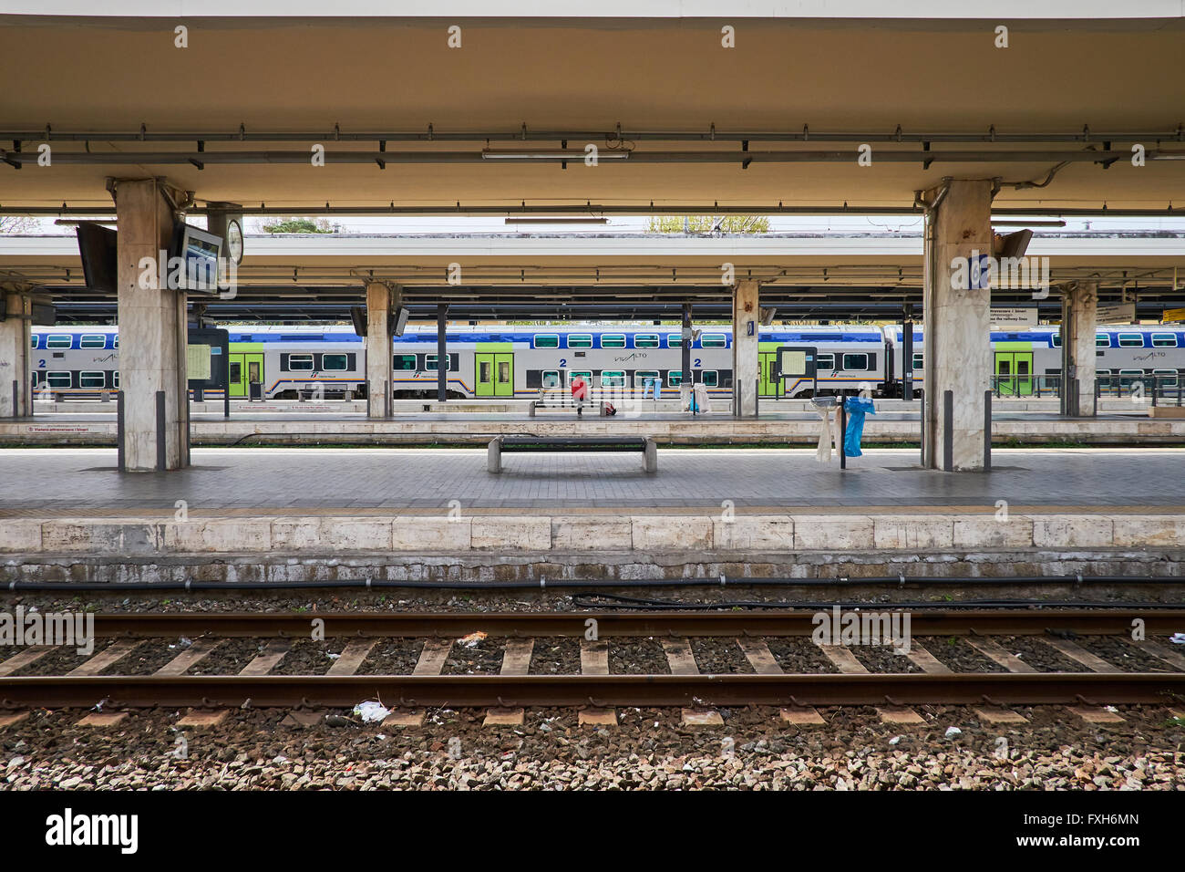 Single person seated on a platform at a train station with a train at a distant platform and rails in the foreground. - Stock Image