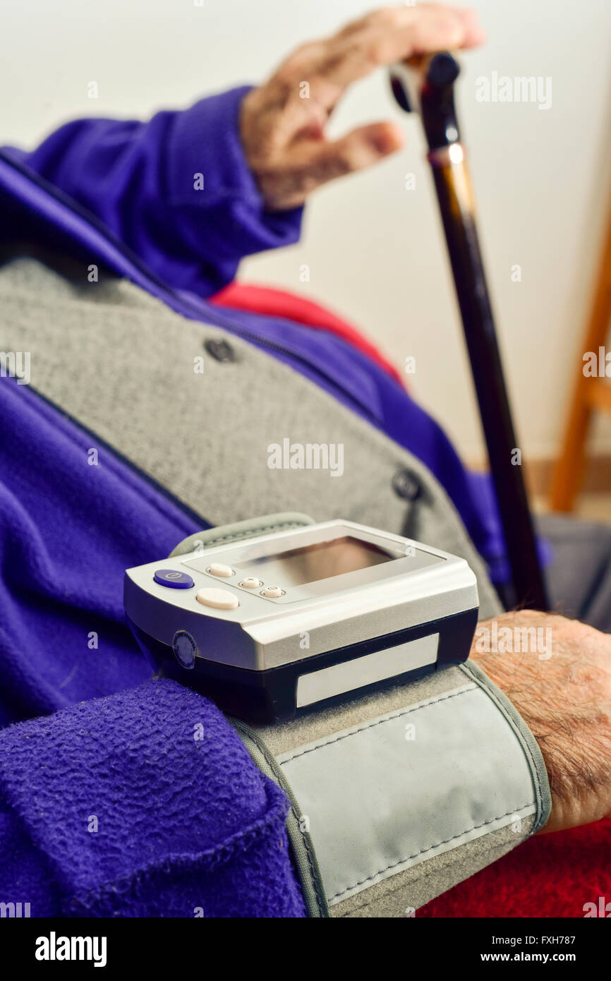 measuring the blood pressure to an old caucasian man with an electronic sphygmomanometer - Stock Image
