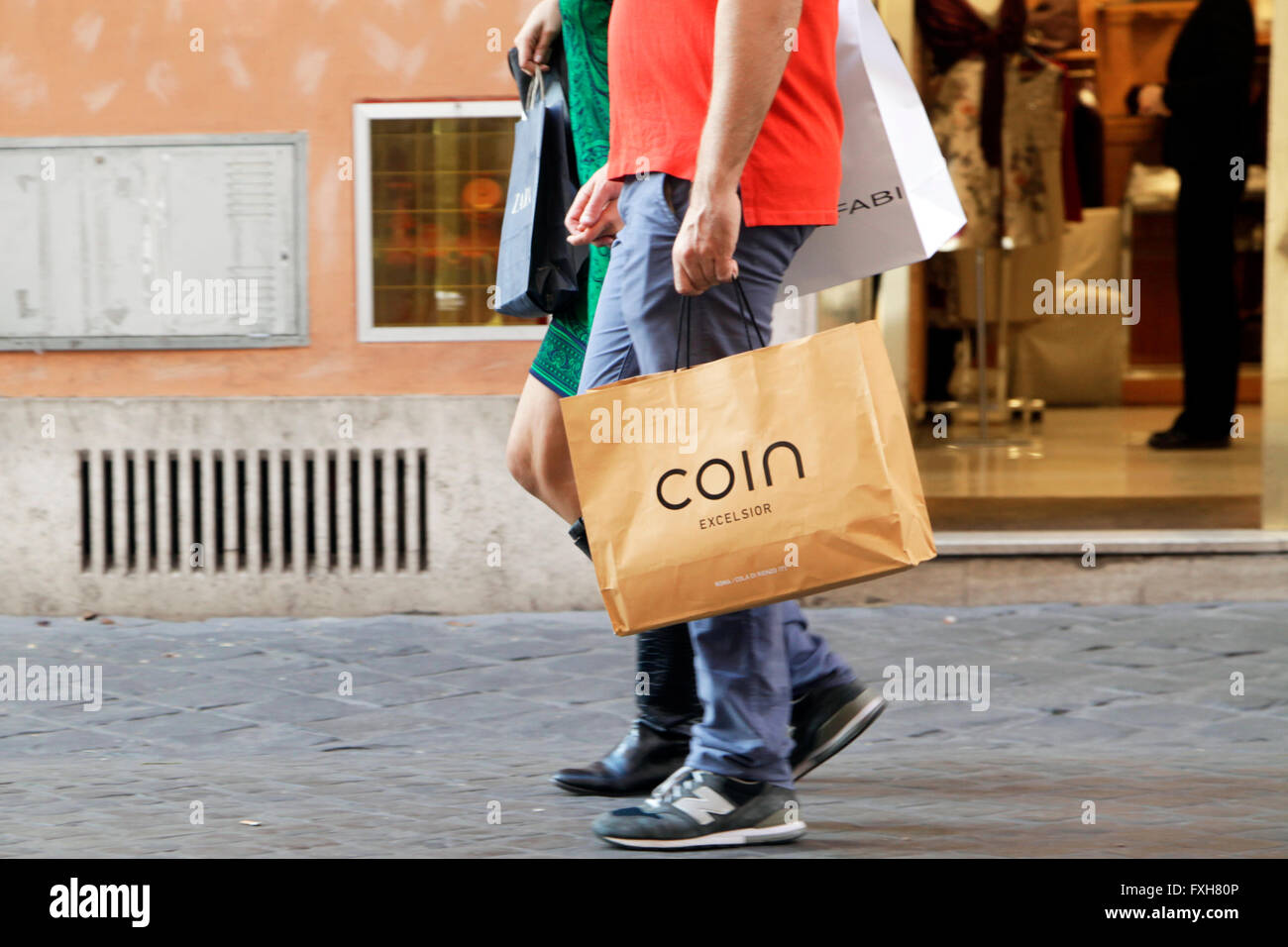 Pedestrian walks with his Coin shopping bag in the center of Rome, Italy - Stock Image