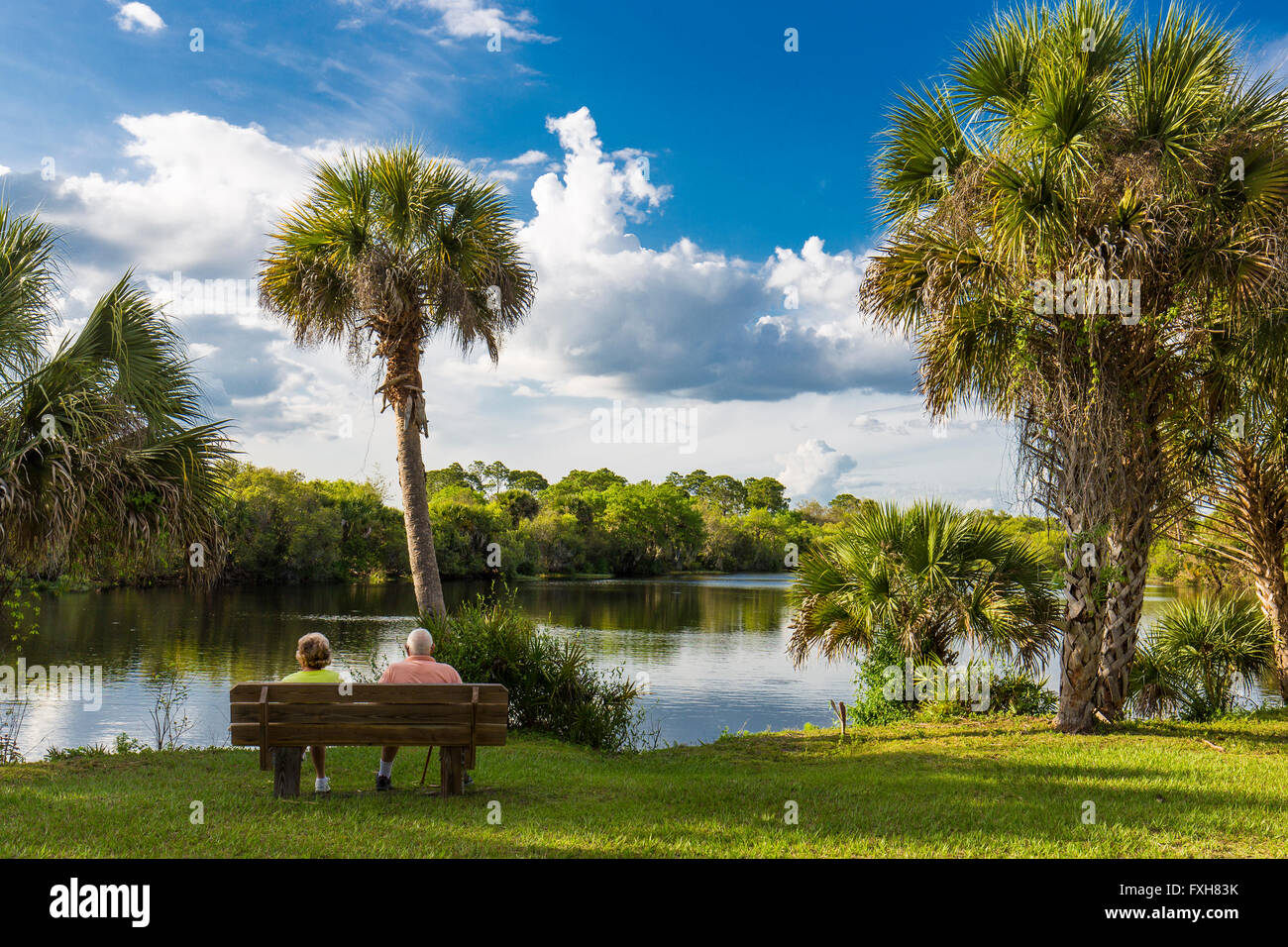Couple sitting on bench overlooking water in Deer Prairie Creek in  Deer Prairie Creek Preserve in Venice Florida Stock Photo
