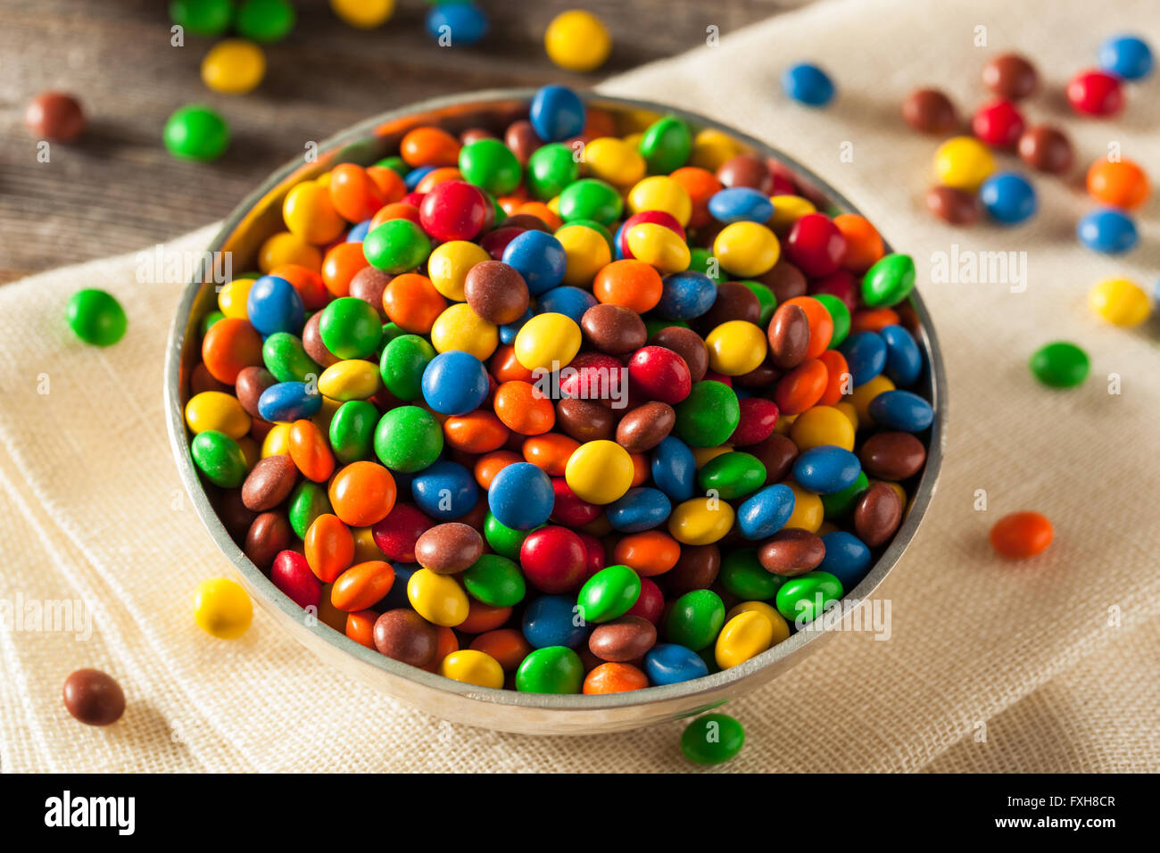 Rainbow Colorful Candy Coated Chocolate Pieces in a Bowl - Stock Image