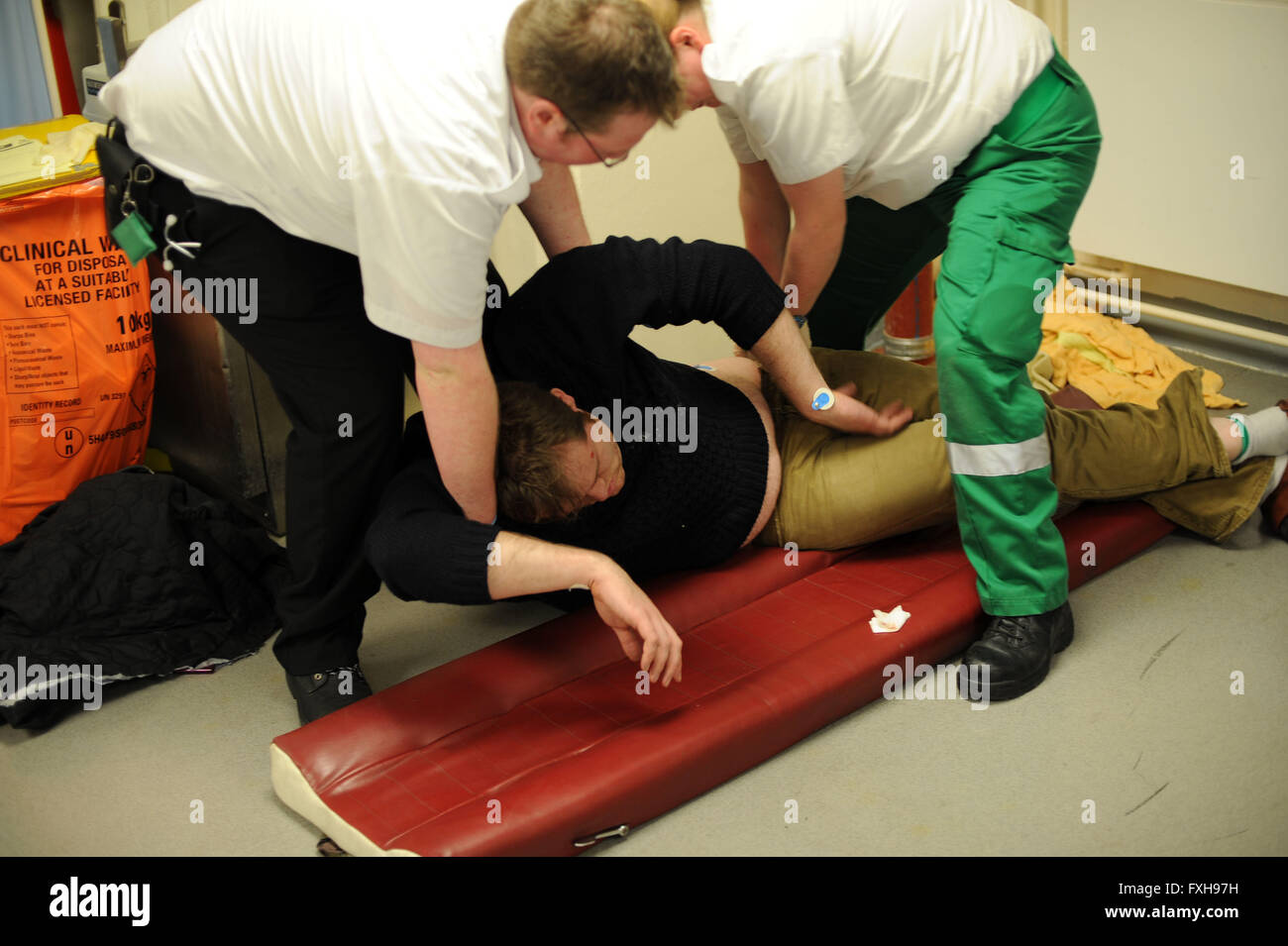 Paramedics provide first aid treatment to a drunken drunk man on black friday in Cardiff, South Wales. - Stock Image