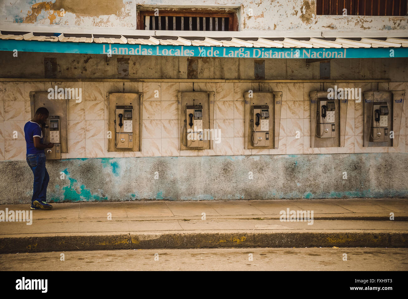 CUBA in December 2015: A male person uses a public payphone to make a call. Public phones are the only telephones - Stock Image