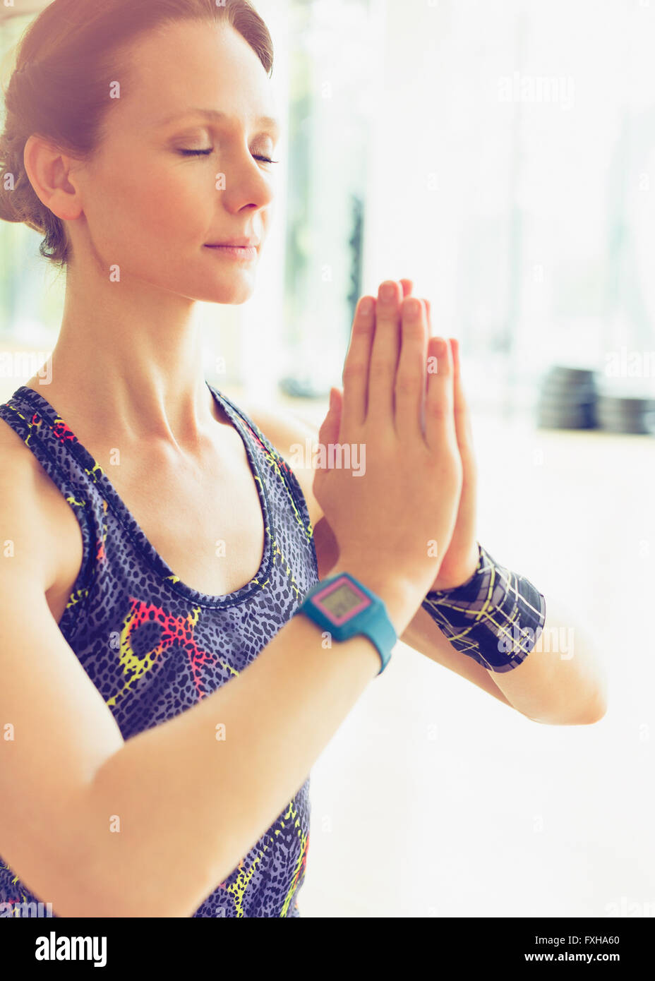 Serene woman practicing yoga with hands clasped - Stock Image